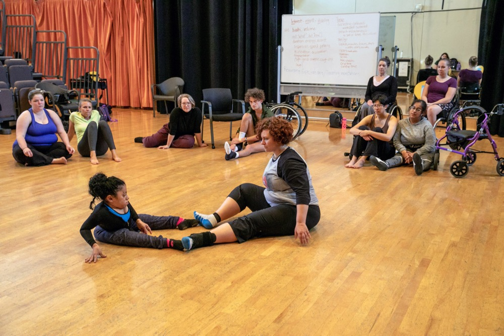 Christelle Dryer, left, and Kelsie Acton work together as the rest of the dancers look on during a workshop, which was part of the UCLA Dancing Disability Lab (Photo by Reed Hutchinson/UCLA)