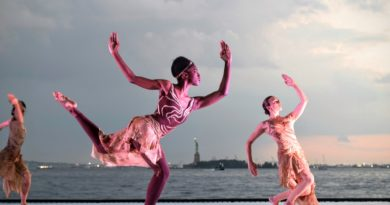Three women dancing on platform with water and cityscape behind them