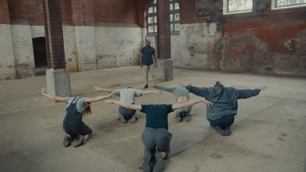 Still from The Conversation featuring group of dancers in an old warehouse